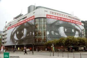 2 riesige Augen vor Kaufhoh-Fassade